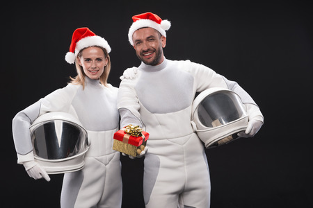 This is for you. Smiling delighted couple of astronauts wearing white protective suit are standing together in red hats and expressing joy while showing box with christmas gift. Isolated background