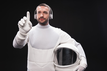 Choose best song. Portrait of pleasant bearded astronaut in headphones is standing in front of transparent screen and pressing on virtual button with concentration. He is holding helmet. Isolated