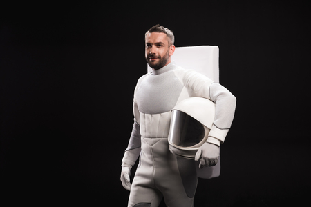 Back at home. Pleasant young astronaut wearing white armor is standing and holding helmet in hands while looking aside confidently. Isolated background with copy space on left side