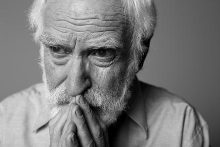 Sluit omhoog zwart-wit portret van oude verontruste gepensioneerde die verdriet uitdrukken. Geïsoleerd op grijze achtergrond