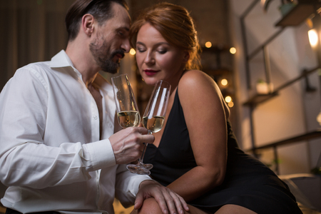 Passionate mature man is touching female leg with desire while holding glasses of champagne. Focus on drink Stock Photo