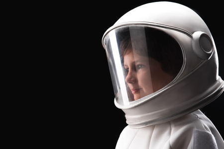Close-up side view of head of little astronaut wearing white helmet and standing while looking aside dreamily. Isolated background with copy space in the left side Фото со стока - 91857809
