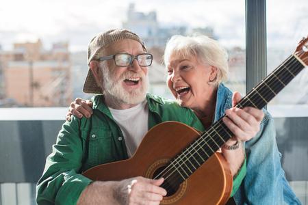 끝없는 햇빛. 웃 고 세 남자와 여자 집에서 악기와 함께 시간을 즐기고의 초상화를 허리. 행복한 은퇴 개념 스톡 콘텐츠