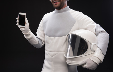 Useful device. Delighted bearded cosmonaut wearing hyperbaric protective costume is standing and holding helmet and mobile phone. He is showing screen of gadget to camera. Isolated background Фото со стока - 91857823