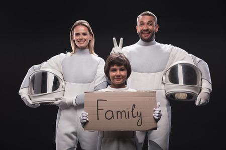 Concetto di famiglia. Il ritratto delle coppie felici dei cosmonauti sta stando insieme al loro figlio. Il bambino sta tenendo la famiglia del segno del cartone mentre esamina la macchina fotografica con gioia. Sfondo isolato Archivio Fotografico - 91857826