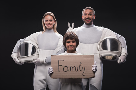 Family concept. Portrait of happy couple of cosmonauts are standing together with their son. Child is holding cardboard sign family while looking at camera with joy. Isolated background