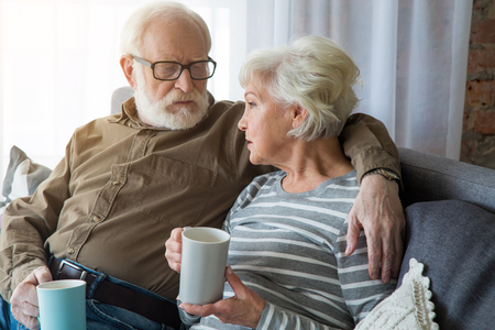 Honest conversation. Portrait of senior couple having dialogue at home while sitting on couch. Husband is cuddling wife while they holding hot cup of tea 스톡 콘텐츠