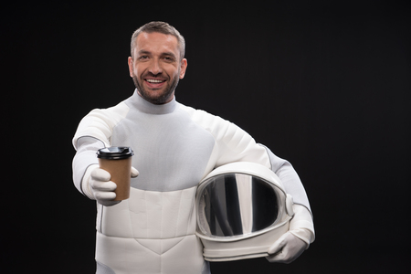Source of energy. Waist-up portrait of positive cosmonaut wearing protective suit is standing and holding helmet and coffee. He is looking at camera with joy. Selective focus and isolated background