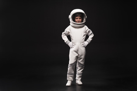 Spaceman concept. Full length portrait of cheerful kid astronaut wearing white protective suit and helmet is standing with arms akimbo while looking at camera with smile. Isolated with copy space Stock Photo