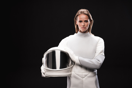 Portrait of confident young female cosmonaut wearing hyperbaric astronaut protective suit is standing and looking at camera seriously while holding helmet. Isolated background Фото со стока