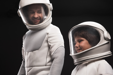 Always together. Optimistic father and his curious son wearing hyperbaric astronaut protective suit are standing and expressing gladness. Man is looking at child with smile. Isolated background Фото со стока - 91857835