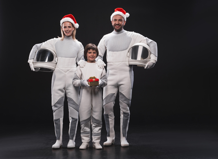 Christmas concept. Full length portrait of family of cosmonauts in red hats are standing together while holding helmets and looking at camera with joy. Little boy is standing with gift box. Isolated Фото со стока