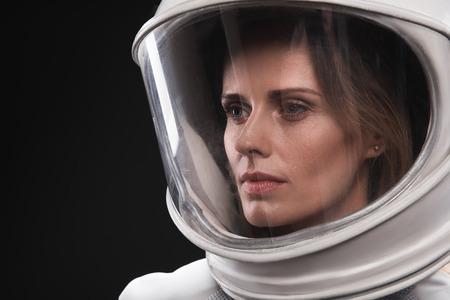 Lost in thoughts. Close-up of face of young serious woman cosmonaut wearing helmet and hyperbaric protective suit is standing and looking aside thoughtfully. Isolated background