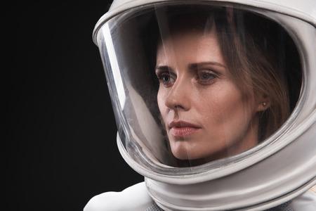 Perso nei pensieri. Il primo piano del fronte del giovane cosmonauta serio della donna che indossa il casco e la tuta protettiva iperbarica è stante e guardando da parte pensieroso. Sfondo isolato Archivio Fotografico - 91857839