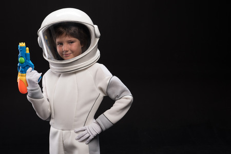 Watchman. Waist up portrait of cosmonaut kid wearing protective costume and helmet is standing with arms akimbo and holding toy gun while looking at camera with joy. Isolated with copy space Stock Photo