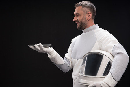Modern technologies. Side view profile of optimistic bristled spaceman wearing protective suit is standing with helmet while holding innovative tablet on his palm. Isolated background