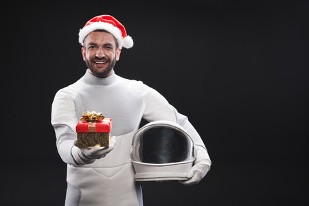 This is yours. Happy bristled young astronaut wearing white protective costume and red santa hat is standing with helmet while holding out box with christmas gift. Isolated with copy space Stock Photo - 91857850