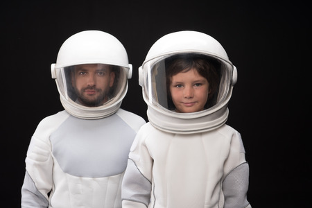 We are best team. Waist up portrait of confident cosmonauts little son and his father. They are standing in helmet and protective costume while looking at camera wistfully. Isolated background