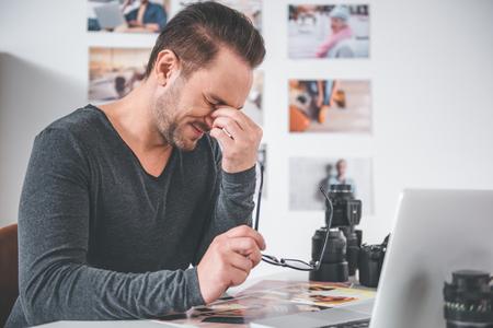 Zijaanzicht vermoeide ongeschoren man aan het werk op Bureau in appartement. Vermoeidheid concept Stockfoto