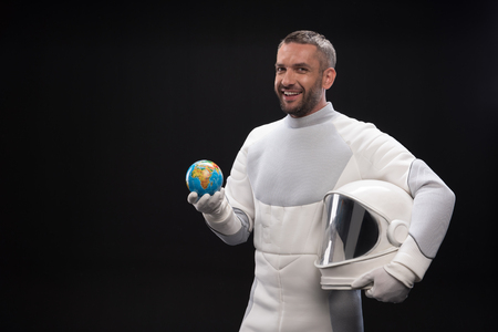 My homeland. Cheerful young bearded astronaut wearing protective costume is standing and holding helmet and small globe of earth while looking at camera with joy. Isolated background and copy space Stock Photo