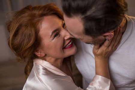 You are my love. Joyful loving couple are looking at each other with happiness and laughing. They are relaxing at home
