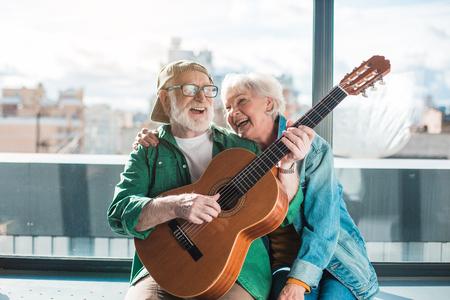 Fiesta musical. Cintura para arriba retrato de hombre casado amoroso y una mujer disfrutando jugando en el instrumento Foto de archivo - 91857873