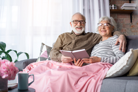 Portrait of lovely married old couple relaxing on couch with pillows at home. Man is hugging woman while they are looking at camera and laughing