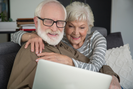 Online communication. Waist up portrait of mature couple looking in notebook with excitement while resting at home. Woman is tightly hugging man while they are laughing