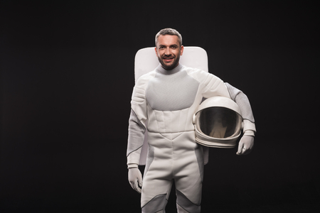 Portrait of happy astronaut is holding helmet while standing in white protective suit. He is looking at camera with joy. Isolated background with copy space in left side. Spaceman concept Stock Photo