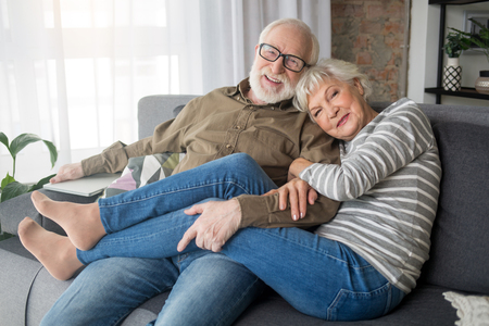 Happy rest. Portrait of delightful senior husband and wife relaxing on couch at home. Woman is tenderly cuddling man, while smiling male tightly hugging her legs