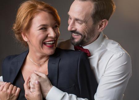 抱きしめて笑う喜びに満ちた愛情のある成熟したカップルの肖像画。思いやりのある紳士は、愛情を持って女性に彼のジャケットを与えています。 写真素材