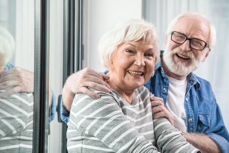 Increíble jubilación. Cintura encima del retrato de dos viejos jubilados alegres que sonríen en la cámara. El esposo está abrazando tiernamente a su esposa mientras está sentado en la ventana Foto de archivo - 91857896