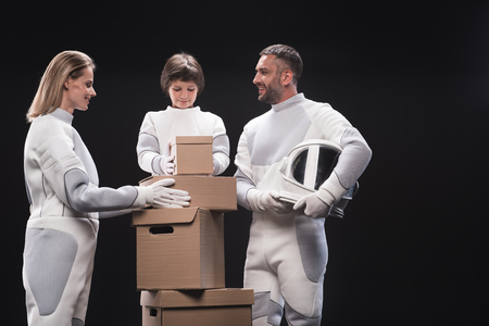 We are team. Cheerful happy family of astronauts wearing specialized protective suit are packing cardboard boxes while preparing for migration to another planet. Isolated. Resettlement concept