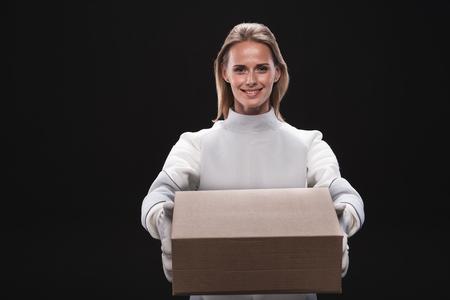 Per te. Il ritratto della donna spaziale attraente piacevole positiva che indossa la tuta protettiva specializzata sta stando e tenendo la scatola di cartone mentre esaminava la macchina fotografica con gioia. Isolato. Concetto di reinsediamento Archivio Fotografico - 91857902