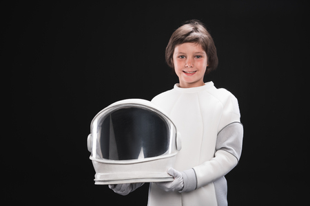 Spaceman concept. Portrait of cheerful little boy wearing white armor is standing and keeping his helmet while looking at camera with joy. Isolated background