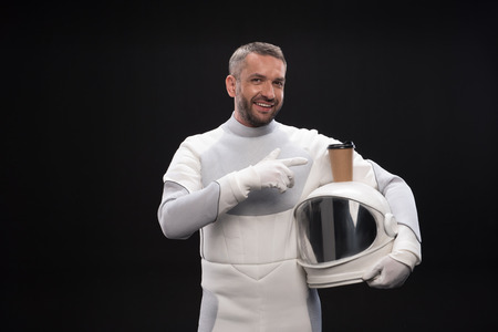 Love this drink. Portrait of happy trained spaceman is standing and pointing on coffee which is on his white helmet while looking at camera with joy. Isolated background