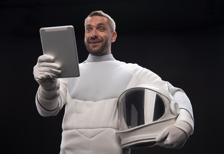 Big shock. Low angle of amazed young bearded spaceman is standing with helmet and modern tablet in his hand. He is looking at screen while opened his mouth in wide-eyed surprise. Isolated background Reklamní fotografie