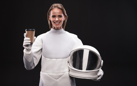 Need some energy. Waist-up portrait of positive young attractive woman astronaut is standing and holding helmet and fresh coffee while looking at camera with joy. Isolated background Фото со стока