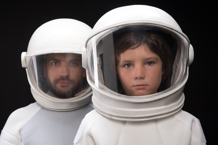 Professional team. Portrait of serious two spacemen are standing together wearing helmet and protective costume. Father and son are looking at camera confidently. Isolated background