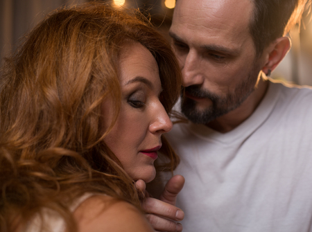 可愛い顔を見せて愛情深い男は優しさで女性の顔に触れている。彼は愛を持つ女性を見ている