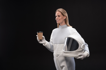 Happy young delightful female cosmonaut wearing protective costume and holding helmet is drinking hot espresso. She is standing and looking aside with joy. Isolated with copy space in the left side