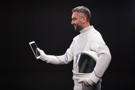 Innovative gadget. Side view profile of pleasant bearded cosmonaut wearing protective costume is standing with helmet and modern tablet in his hands. He is looking at screen with smile. Isolated