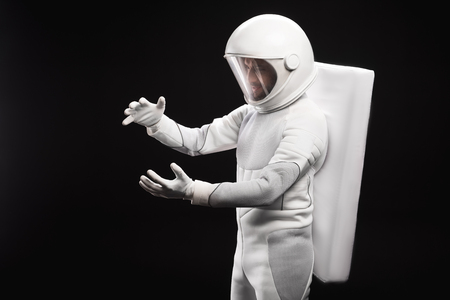 New discovery. Side view of concentrated young astronaut wearing specialized protective suit and helmet is standing and holding important unidentified object. Isolated background