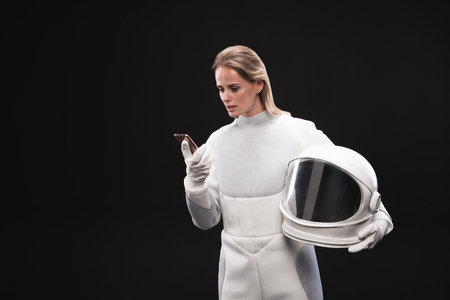 Important call. Serious young lady astronaut is holding helmet and modern mobile phone while looking at screen of gadget with concentration. Isolated with copy space in the left side Фото со стока