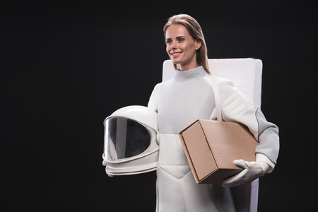 Ready for change. Pleasant optimistic spacewoman wearing protective suit is holding cardboard box and helmet. She is going to spaceship while is looking aside with smile. Isolated with copy space