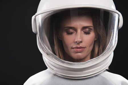 Keep calm. Close-up portrait of attractive spacewoman wearing helmet and protective costume is standing with closed eyes. Isolated background. Cosmos concept Фото со стока