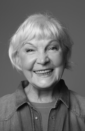 Close up black-and-white portrait of mature lady smiling while standing. Isolated on grey background