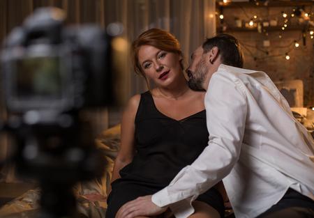 情熱的な男はベッドに座っている間、女性の首にキスしています。女性は自信を持ってカメラを見ています。新しい体験コンセプト