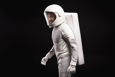 Side view of cheerful young male astronaut wearing helmet and hyperbaric astronaut protective suit is hardly moving. He is looking aside with smile. Isolated background. Cosmonaut concept