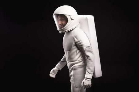 Zijaanzicht van vrolijke jonge mannelijke astronaut met helm en hyperbaar astronaut beschermend pak beweegt nauwelijks. Hij kijkt opzij met een glimlach. Geïsoleerde achtergrond. Kosmonaut concept Stockfoto